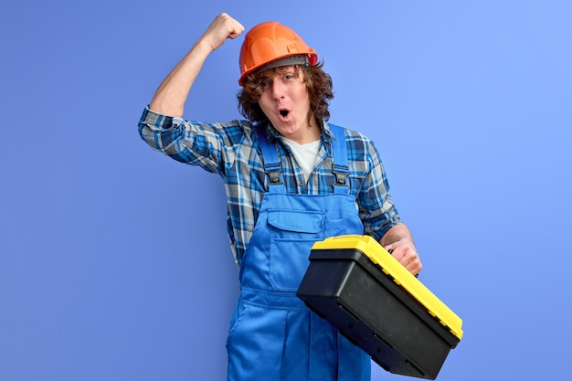 Jonge mannelijke ingenieur in blauwe overall kloppen op oranje helm, zorgen ervoor dat werknemers met goede bescherming werken