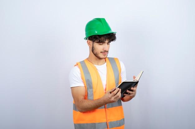 Jonge mannelijke ingenieur in groene bouwvakker die nota's op witte achtergrond leest. hoge kwaliteit foto
