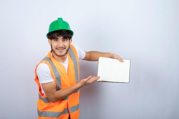 Jonge mannelijke ingenieur in groene bouwvakker die nota's over witte achtergrond toont. hoge kwaliteit foto