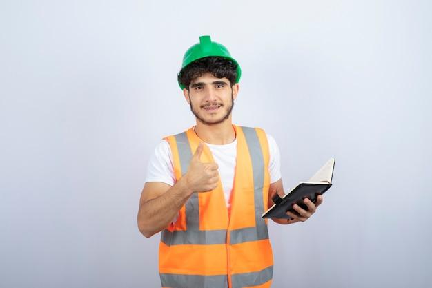 Jonge mannelijke ingenieur in het groene notitieboekje van de bouwvakkerholding op witte achtergrond. hoge kwaliteit foto