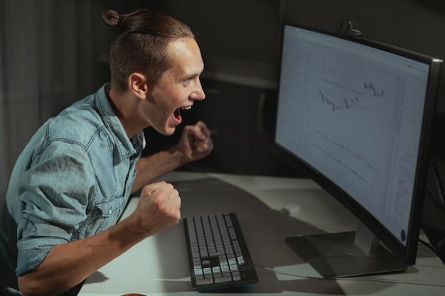 Jonge mannelijke it-industrie die freelancer laat in de nacht werkt