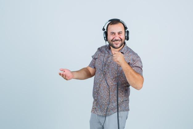 Jonge mannelijke kabel van gsm terwijl glimlachen naar de camera in casual shirt, broek en energiek, vooraanzicht kijken.