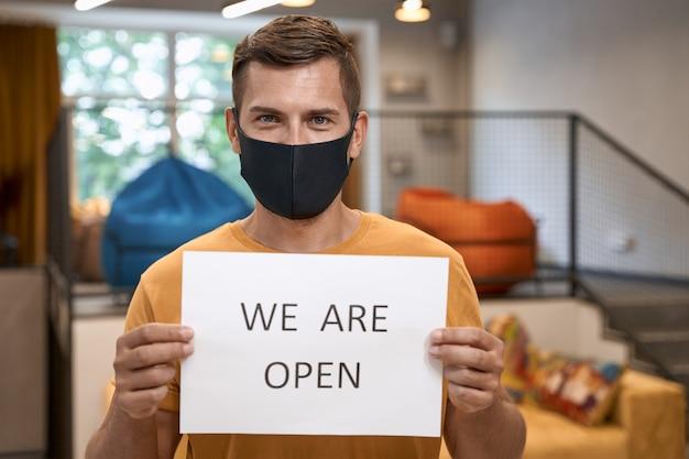 Jonge mannelijke kantoormedewerker met een zwart beschermend masker met papier met tekst dat we open zijn voor de camera