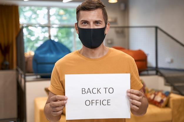 Jonge mannelijke kantoormedewerker met een zwart beschermend masker met papier met tekst terug naar kantoor op