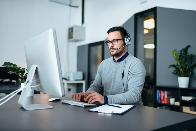 Jonge mannelijke klantenondersteuning met hoofdtelefoon die aan de computer werkt.