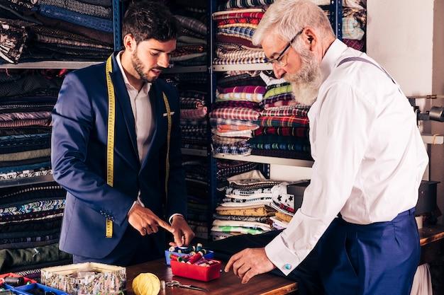 Jonge mannelijke kleermaker die kleurrijke spoel tonen aan zijn klant in de winkel