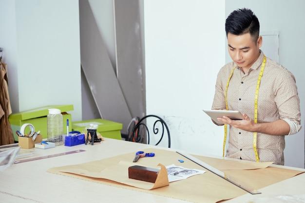 Jonge mannelijke kleermaker die zijn aantekeningen op tabletcomputer controleert bij het tekenen van een naaipatroon op een groot vel papier