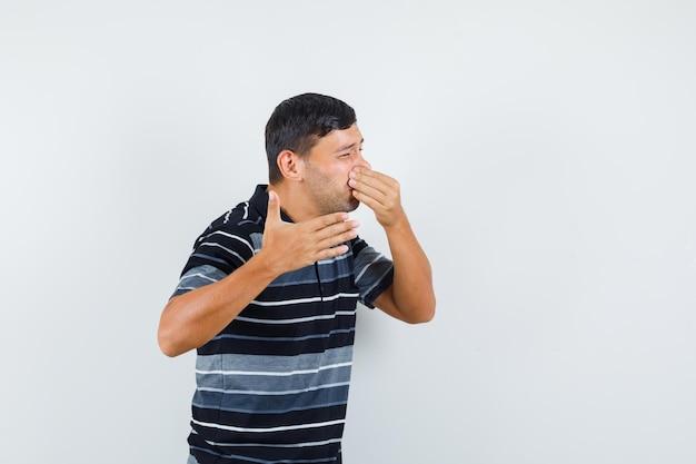 Jonge mannelijke knijpende neus als gevolg van een slechte geur in t-shirt en er walgelijk uitzien. vooraanzicht.