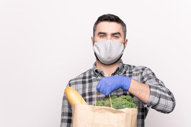 Jonge mannelijke koerier in beschermend masker en handschoenen die afzonderlijk brood en groenten bij u thuis bezorgen in een papieren pakket