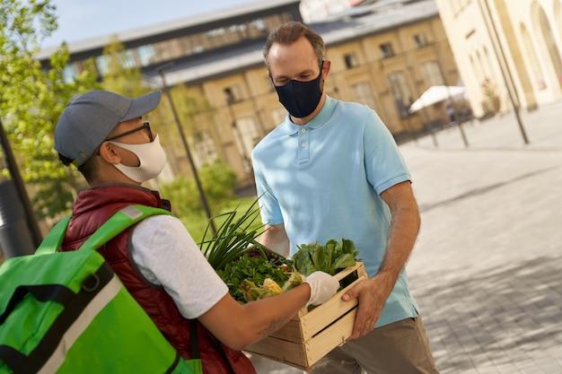 Jonge mannelijke koerier in beschermend masker en handschoenen die houten b . geven