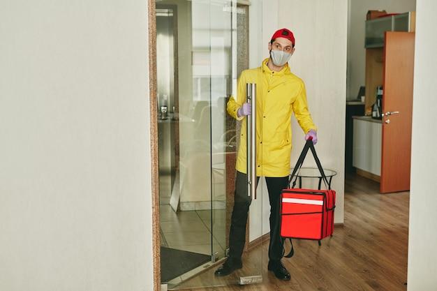 Jonge mannelijke koerier in uniform, beschermend masker en handschoenen met grote rode zak bij het betreden van een modern kantoor en het bezorgen van voedsel
