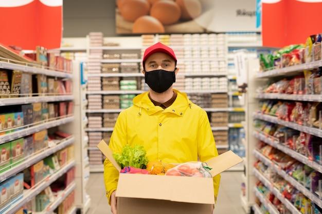 Jonge mannelijke koerier in uniform en beschermend masker die tussen grote displays in de supermarkt staat en een doos met verse producten vasthoudt