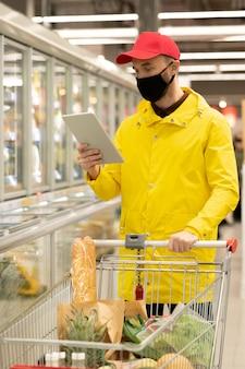 Jonge mannelijke koerier in uniform en beschermend masker kijkt door online bestellingen van klanten terwijl hij de kar met verse producten in de supermarkt duwt