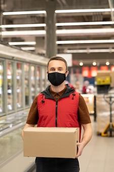 Jonge mannelijke koerier in uniform en beschermend masker staat bij een groot display in de supermarkt en houdt een verpakte doos met verse producten vast