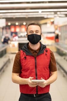 Jonge mannelijke koerier in uniform en beschermend masker staat in grote supermarkt en kijkt door online bestellingen in touchpad