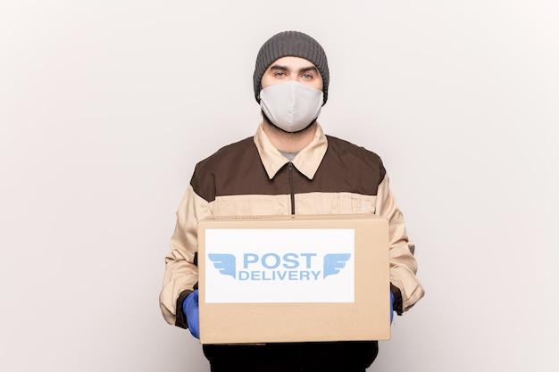 Jonge mannelijke koerier in werkkleding, beschermende handschoenen en gasmasker met een grote kartonnen doos tijdens het bezorgen van uw online winkelbestelling