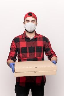 Jonge mannelijke koerier in werkkleding, masker en handschoenen terwijl je twee grote kartonnen vierkante dozen met bestelde pizza krijgt