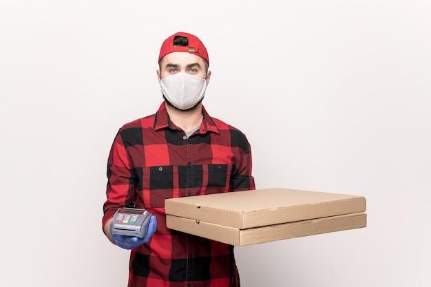 Jonge mannelijke koerier met afgeleverde pizzahoudingsautomaat in afwachting van betaling van de bestelling
