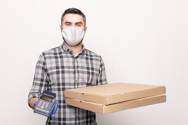Jonge mannelijke koerier uit café met twee grote vierkante kartonnen dozen en een betaalautomaat terwijl hij je bestelde pizza bezorgt