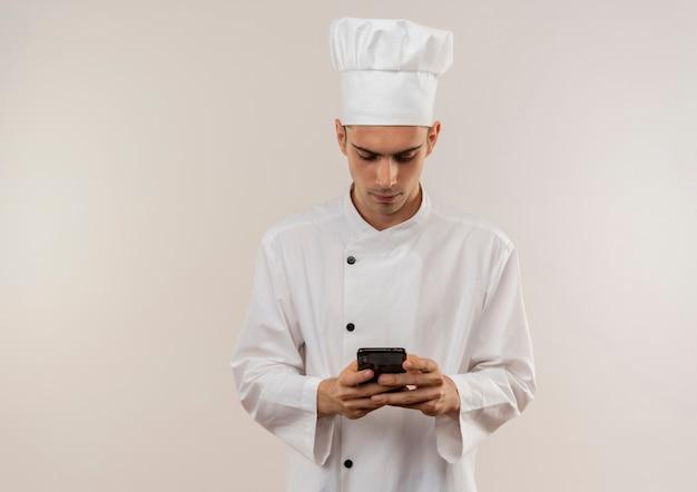 Jonge mannelijke kok die chef-kok eenvormig nummer op telefoon met exemplaarruimte draagt