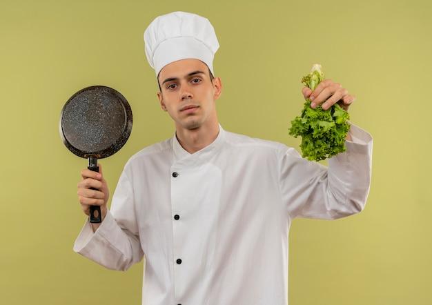 Jonge mannelijke kok die eenvormige chef-kok draagt die koekenpan en salade in zijn hand op geïsoleerde groene muur opheft
