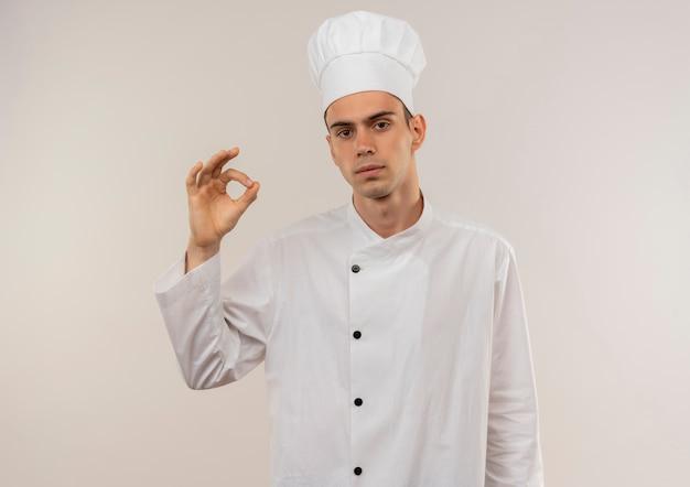 Jonge mannelijke kok die eenvormige chef-kok draagt die ok gebaar op geïsoleerde witte muur met exemplaarruimte toont