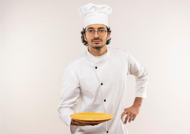 Jonge mannelijke kok die eenvormige chef-kok en glazen draagt die plaat houdt en hand op heup zet
