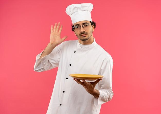 Jonge mannelijke kok die eenvormige chef-kok en glazen draagt die plaat houdt en hand opheft