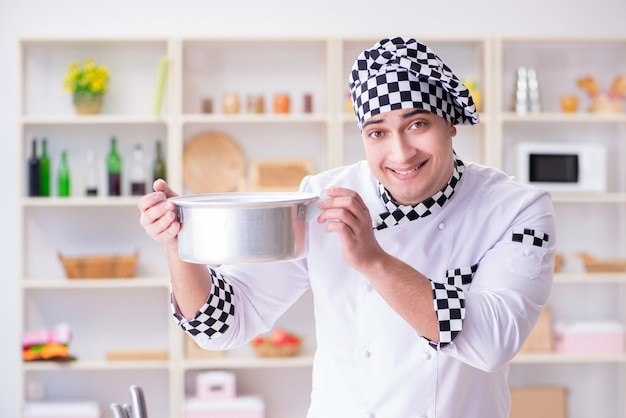 Jonge mannelijke kok die in de keuken werkt