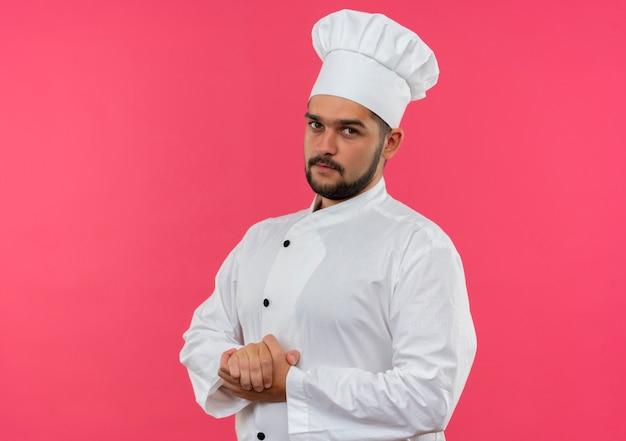 Jonge mannelijke kok die in eenvormige chef-kok handen samen houdt die geïsoleerd op roze ruimte kijken