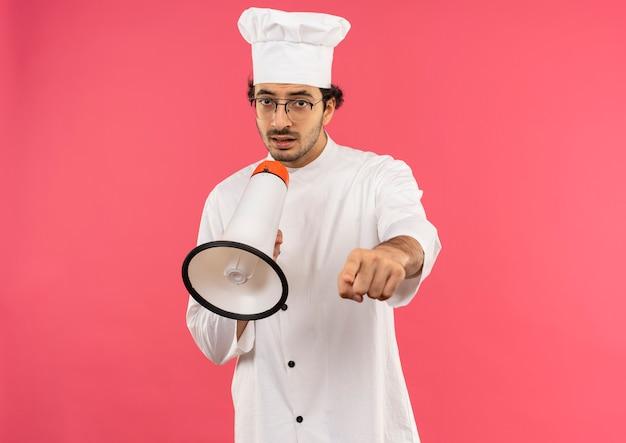 Jonge mannelijke kok die uniform van de chef-kok en glazen draagt, spreekt op luidspreker en toont u gebaar