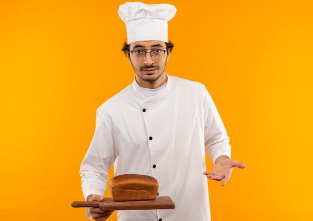 Jonge mannelijke kok die uniforme chef-kok en glazen draagt die brood op scherpe raad houdt