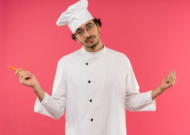 Jonge mannelijke kok die uniforme chef-kok en glazen draagt die wortel houdt en vuisten spreidt