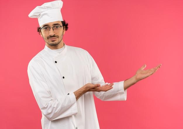 Jonge mannelijke kok die uniforme chef-kok en glazen punten met handen aan kant draagt