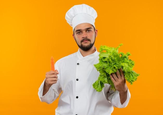 Jonge mannelijke kok in chef-kok eenvormige holdingssla en wortel die geïsoleerd op oranje ruimte kijken