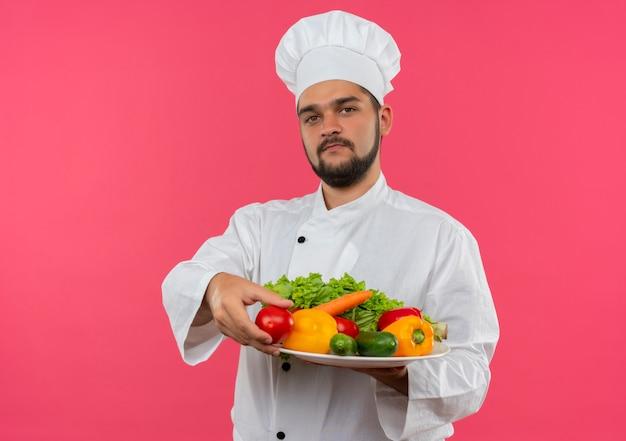 Jonge mannelijke kok in chef-kok eenvormige plaat van groenten en tomaat en kijken geïsoleerd op roze ruimte