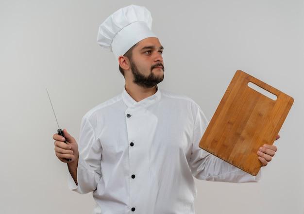 Jonge mannelijke kok in chef-kok het eenvormige mes en scherpe raad die kant bekijken die op witte ruimte wordt geïsoleerd