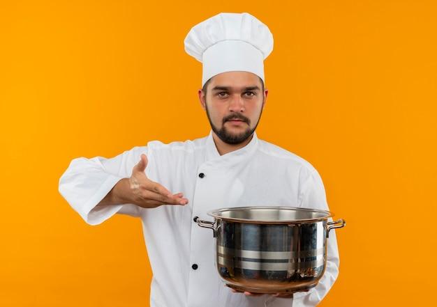 Jonge mannelijke kok in chef-kok uniform bedrijf en wijzend met hand op pot en kijken geïsoleerd op oranje ruimte