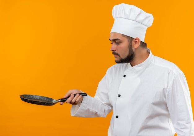 Jonge mannelijke kok in chef-kok uniform houden en kijken naar koekenpan geïsoleerd op oranje ruimte