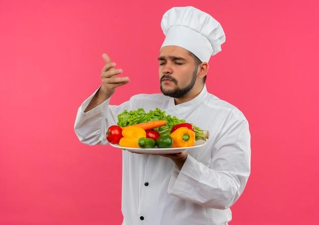 Jonge mannelijke kok in chef-kok uniform houden en snuiven plaat van groenten met gesloten ogen geïsoleerd op roze ruimte