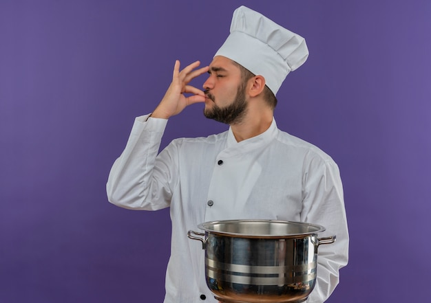Jonge mannelijke kok in chef-kok uniforme pot houden en lekker gebaar geïsoleerd op paarse ruimte doen