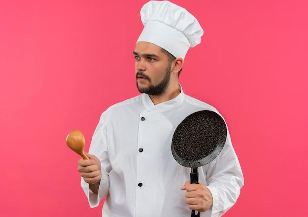Jonge mannelijke kok in de lepel en de koekenpan van de chef-kok eenvormige holding die kant bekijken die op roze ruimte wordt geïsoleerd