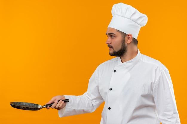Jonge mannelijke kok in de pan van de chef-kok de eenvormige holding en bekijkt kant die op oranje ruimte wordt geïsoleerd
