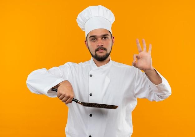 Jonge mannelijke kok in de pan van de chef-kok de eenvormige holding en doet ok teken dat op oranje ruimte wordt geïsoleerd
