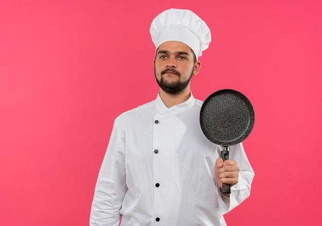 Jonge mannelijke kok in de pan van de chef-kok de eenvormige holding en kijkt recht geïsoleerd op roze ruimte