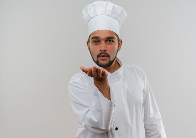Jonge mannelijke kok in eenvormige chef-kok die klapkus naar camera verzendt