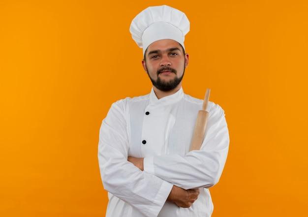 Jonge mannelijke kok in eenvormige chef-kok die zich met gesloten houding en bedrijf bevindt