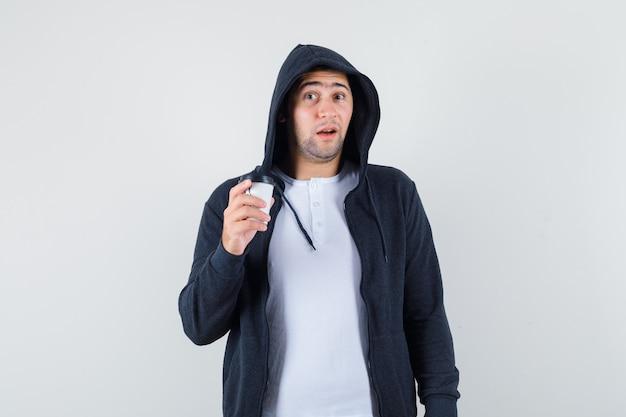 Jonge mannelijke kop van koffie in t-shirt, jasje en op zoek verbaasd te houden. vooraanzicht.