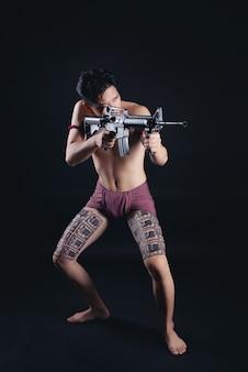 Jonge mannelijke krijger thailand poseren in een vechthouding met een vuurwapen