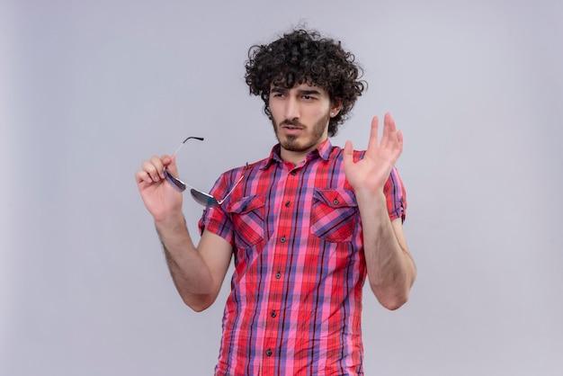 Jonge mannelijke krullend haar geïsoleerd kleurrijke overhemd zonnebril nee zeggen